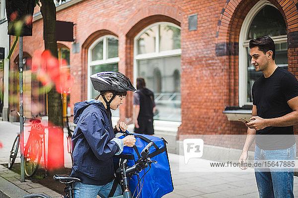 Lieferfrau öffnet Tasche  während ein männlicher Kunde in der Stadt auf dem Bürgersteig steht