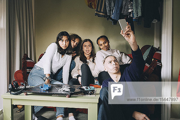 Friends taking selfie on smart phone while making faces in living room at home
