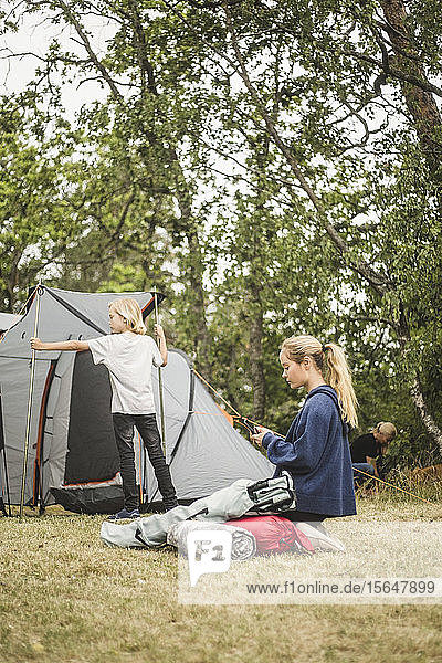 Teenage girl using phone while family pitching tent at camping site