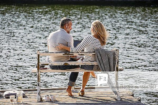 Rückansicht eines Paares  das sich unter Verwendung eines Laptops auf einer Bank über dem Pier am See unterhält