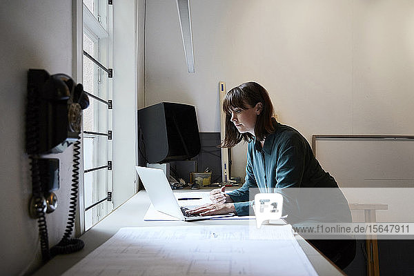 Confident female architect using laptop in office