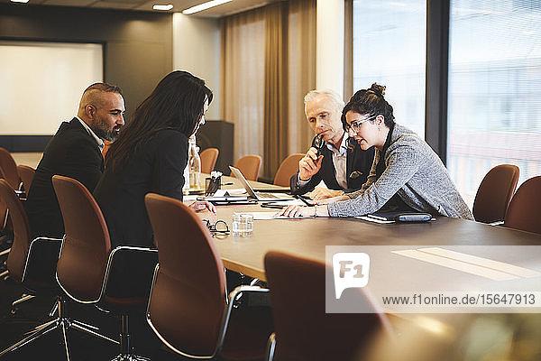 Männliche und weibliche Anwälte diskutieren über Dokument am Konferenztisch in einer Sitzung