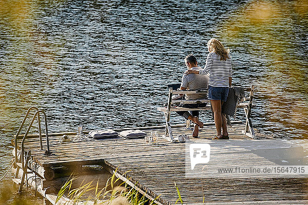 Woman standing by man working on laptop while female executive standing on wooden pier against lake