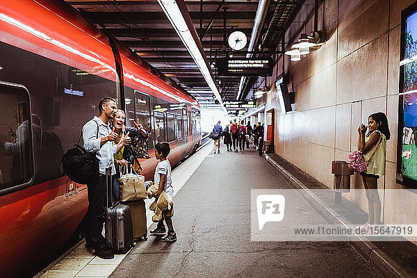 Girl photographing family standing with luggage against train at railroad station