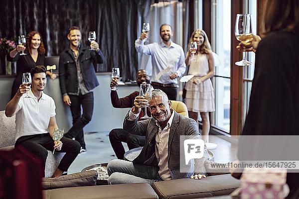 Geschäftsleute  die während der Konferenz Weingläser erheben