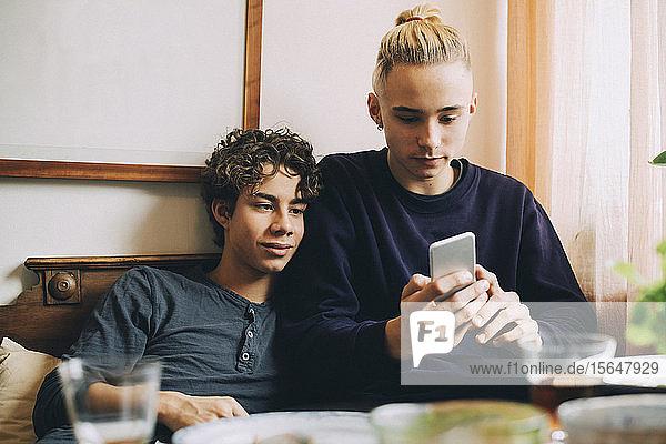 Jungen im Teenageralter  die zu Hause auf dem Sofa liegend ein Mobiltelefon benutzen
