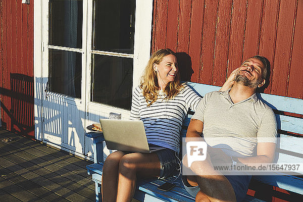Happy woman using laptop while playing with man on bench at porch during summer