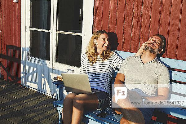 Glückliche Frau  die im Sommer mit einem Laptop spielt  während sie mit einem Mann auf einer Bank auf der Veranda spielt