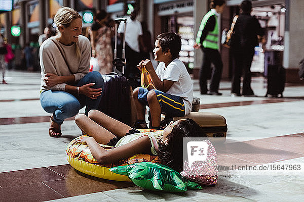Mutter spricht mit Kindern  während sie am Bahnhof wartet