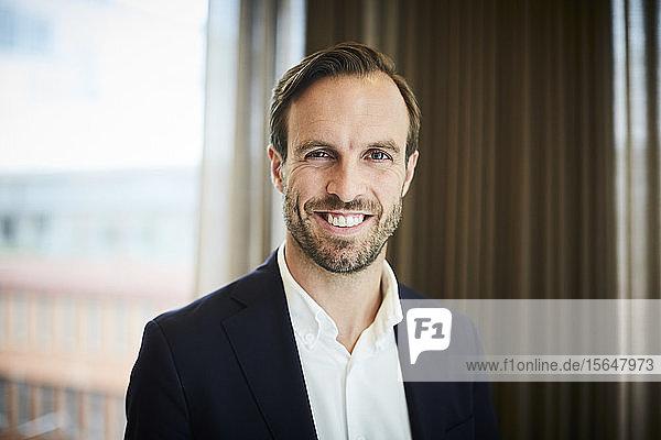 Porträt eines Anwalts der glücklichen Mitte der Erwachsenen in Formalitäten am Arbeitsplatz