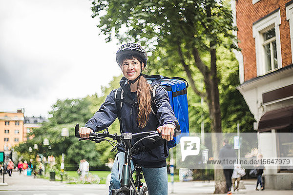 Smiling food delivery woman with bicycle on street in city