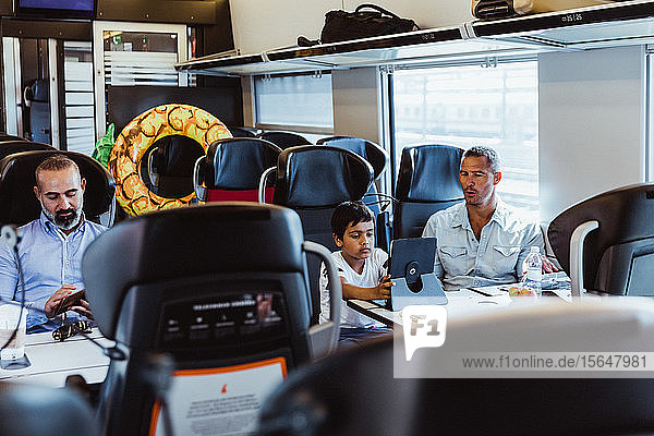 Father looking at son using digital tablet and businessman working at desk in train