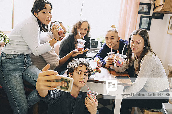 Teenage boy taking selfie with friends through mobile phone while enjoying smoothie at home