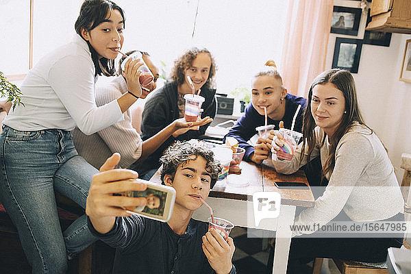 Teenager Junge nimmt Selfie mit Freunden über Handy mit  während er zu Hause einen Smoothie genießt