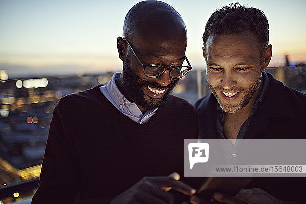 Lächelnde männliche Berufstätige  die während des Sonnenuntergangs auf der Terrasse stehen und auf ihr Handy schauen