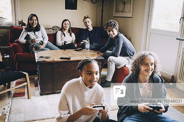 Lächelnde Männer und Frauen spielen Videospiele  während Freunde zu Hause im Hintergrund sitzen