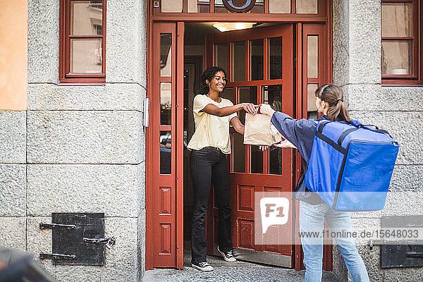 Lebensmittellieferantin  die ein Paket an einen Kunden ausliefert  der am Eingang der Stadt steht