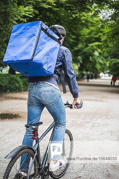 Rückansicht eines Lebensmittellieferanten  der auf der Straße in der Stadt Fahrrad fährt
