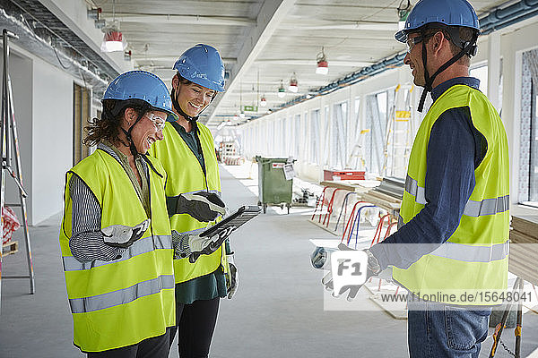 Smiling male and female architects discussing over digital tablet at construction site