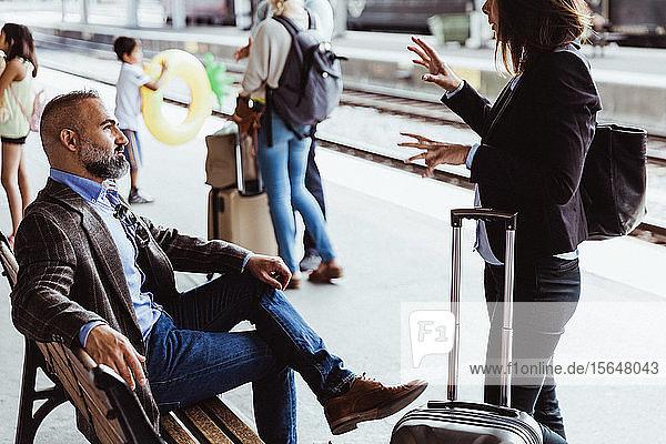 Geschäftskollegen diskutieren während sie am Bahnhof warten