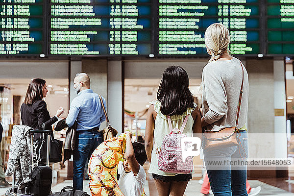 Familien- und Geschäftskollegen  die beim Warten am Bahnhof auf die Ankunft-Abfahrtstafel schauen
