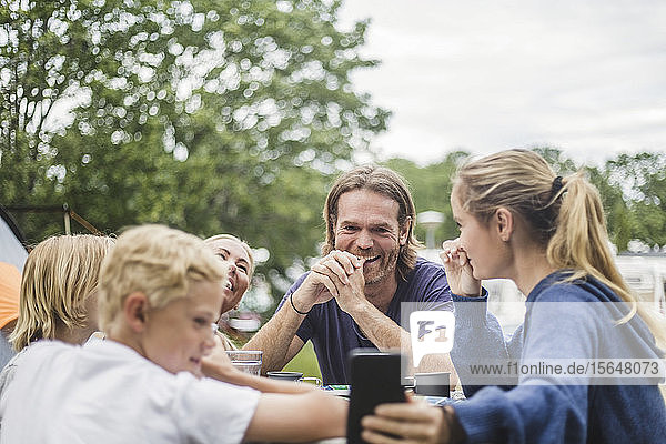 Teenage girl taking selfie with family on table at camping site