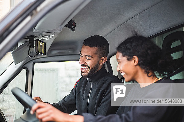 Smiling male mover showing mobile phone to coworker while sitting in truck