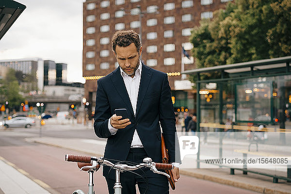 Businessman using mobile phone while standing with bicycle on street in city