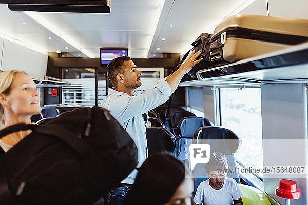 Mittelgroßer erwachsener Mann arrangiert Koffer auf dem Regal im Zug während einer Familienreise