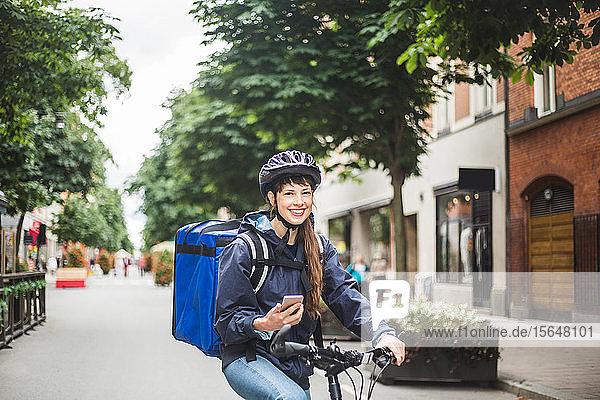 Porträt einer lächelnden Essenslieferantin mit Fahrrad auf der Straße