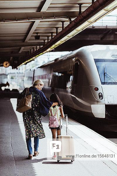 Mutter und Tochter in voller Länge mit Gepäck gehen auf dem Bahnsteig am Bahnhof