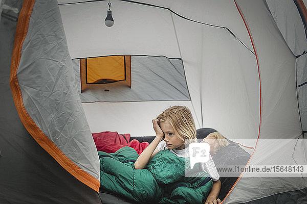 Mädchen reibt sich beim Aufwachen von Bruder im Zelt beim Camping die Augen