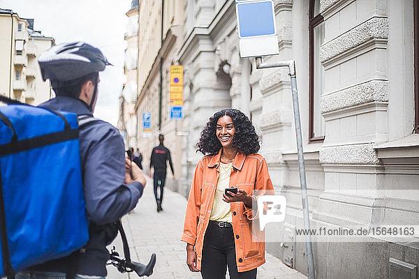 Lächelnde Kundin unterhält sich mit Essenslieferant  während sie auf dem Bürgersteig steht