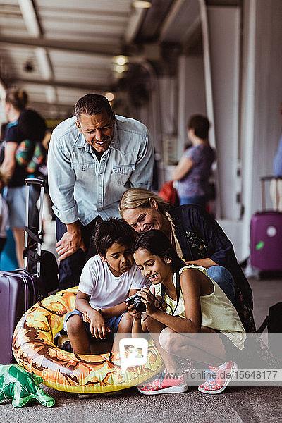 Glückliche Familie schaut in die Kamera auf dem Bahnsteig des Bahnhofs