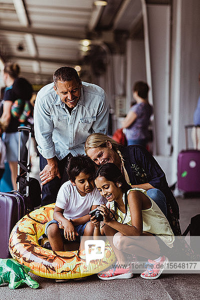 Happy family looking at camera on railroad station platform