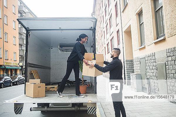 Lächelnde männliche und weibliche Möbelpacker beim Entladen der Kiste vom Lastwagen auf der Straße in der Stadt