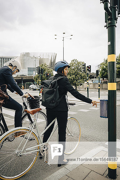 Businesswoman with bicycle using walk signal on street in city