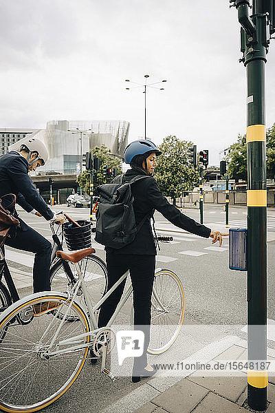 Geschäftsfrau mit Fahrrad  die ein Fußgängersignal auf der Straße in der Stadt benutzt