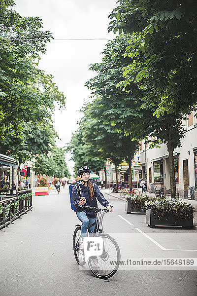 Food delivery woman with bicycle on street in city
