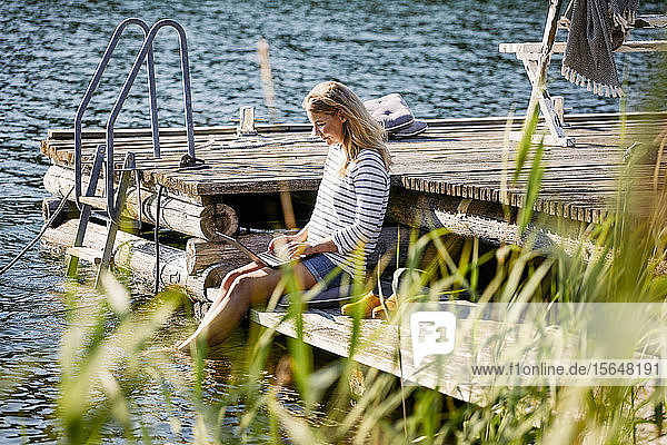 Mid adult female using laptop while sitting on jetty during summer