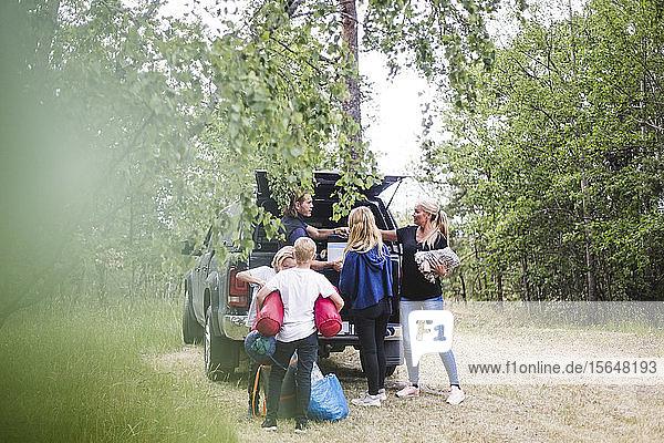Eltern mit Kindern  die im Urlaub auf dem Campingplatz Gepäck aus dem Auto ausladen