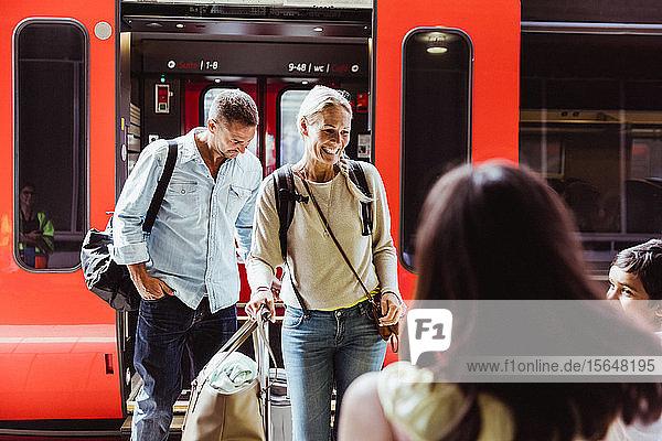 Glückliche Familie mit Gepäck steht am Bahnsteig gegen den Zug