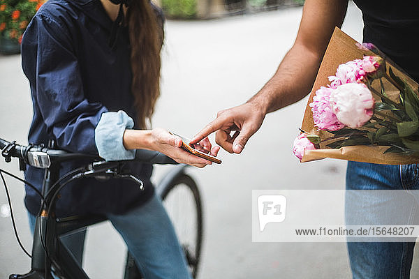 Midsection of delivery woman taking sign from male customer while delivering bouquet on street in city