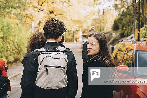 Porträt einer Teenagerin  die mit Freundinnen und Freunden in der Stadt unterwegs ist