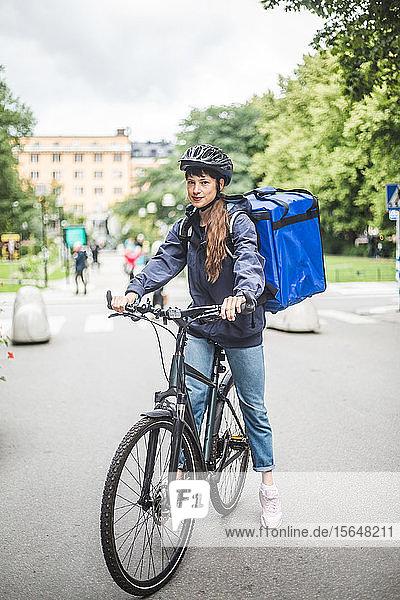 Porträt einer selbstbewussten Essenslieferantin mit Fahrrad auf der Straße in der Stadt