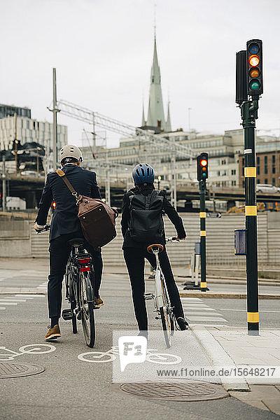 Rückansicht eines Geschäftsmannes und einer Geschäftsfrau mit Fahrrädern auf der Stadtstraße