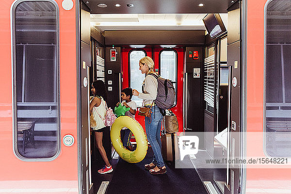 Mother and children with luggage walking in train at station