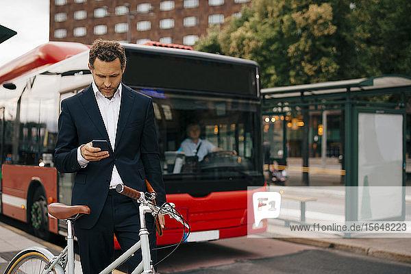 Geschäftsmann benutzt Smartphone  während er mit dem Fahrrad gegen den Bus auf der Straße in der Stadt steht