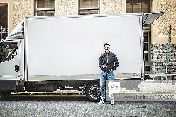 Porträt eines männlichen Fahrers  der auf einer Straße in der Stadt gegen einen Lastwagen steht