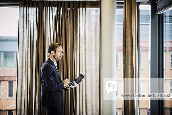 Seitenansicht eines mittelgroßen erwachsenen Anwalts  der einen blauen Zahn trägt  während er seinen Laptop im Büro benutzt